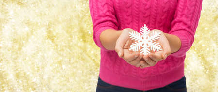 christmas, holidays and people concept - close up of woman in pink sweater holding snowflake decoration over yellow lights photo