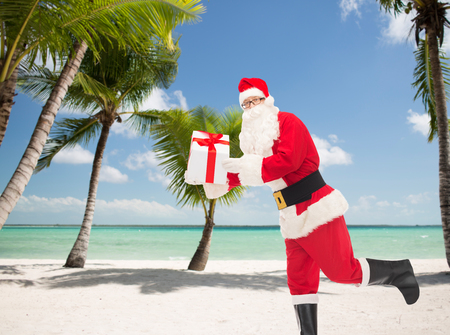 christmas, holidays, travel and people concept - man in costume of santa claus running with gift box over tropical beach  photo