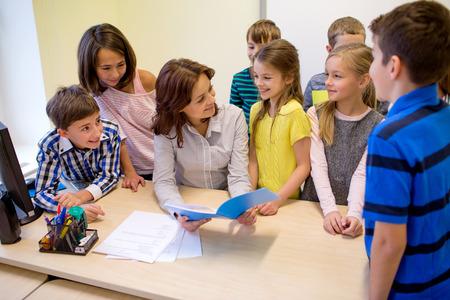 maestra: educación, escuela primaria, el aprendizaje y el concepto de la gente - grupo de niños de la escuela con el profesor hablando en el aula Foto de archivo