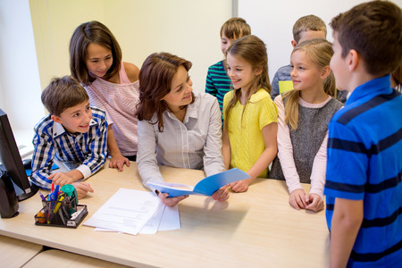 teacher: education, elementary school, learning and people concept - group of school kids with teacher talking in classroom