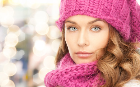 pink hat: happiness, winter holidays, christmas and people concept - close up of young woman in pink hat and scarf over lights background Stock Photo