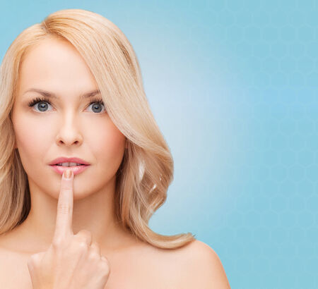 cold sore: health, people and beauty concept - beautiful young woman touching her lips over blue background