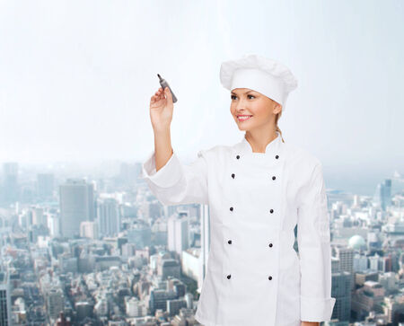 people, cooking and advertisement concept - smiling female chef, cook or baker with marker writing something on virtual screen over city background photo