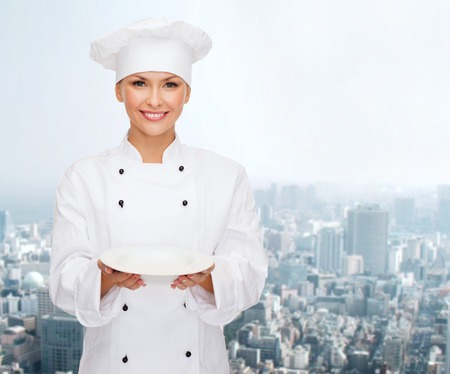 people, cooking and food concept - smiling female chef, cook or baker with empty plate over city background photo