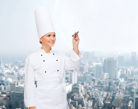people, cooking and advertisement concept - smiling female chef, cook or baker with marker writing something on air over city background photo