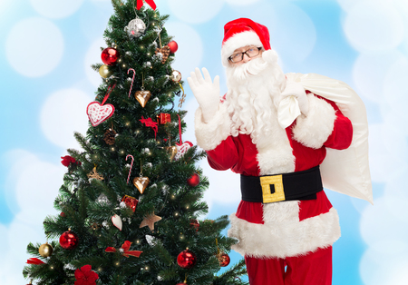 christmas, holidays and people concept - man in costume of santa claus with bag and christmas tree waving hand over blue lights background photo