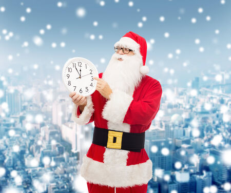 twelve month old: christmas, holidays and people concept - man in costume of santa claus with clock showing twelve pointing finger over snowy city background