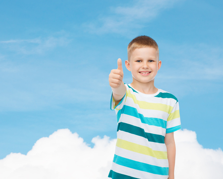pre approval: happiness, childhood and people concept - smiling little boy in casual clothes showing thumbs up over blue sky background Stock Photo