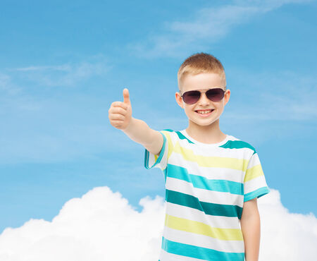 pre approval: happiness, summer, childhood, gesture and people concept - smiling cute little boy in sunglasses over blue sky background showing thumbs up Stock Photo