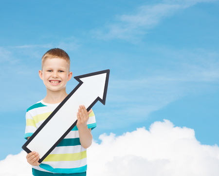 directive: advertising, direction and childhood concept - smiling little boy with white blank arrow pointing up over blue sky