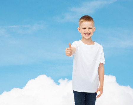 pre approval: advertising, dream, gesture, people and childhood concept - smiling little boy in white blank t-shirt showing thumbs up over sky background