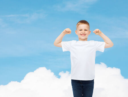 advertising, dream, people and childhood concept - smiling little boy in white blank t-shirt with raised hands over sky background photo