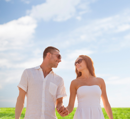 love, people, summer and relations concept - smiling couple wearing sunglasses walking outdoors over blue sky and grass background photo