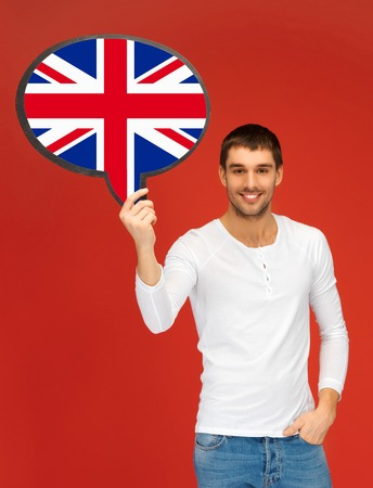 english text: education, fogeign language, english, people and communication concept - smiling young man holding text bubble of british flag Stock Photo