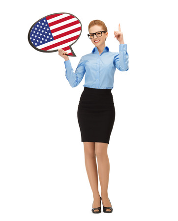 education, foreign language, english, people and communication concept - smiling woman holding text bubble of american flag and pointing finger up photo
