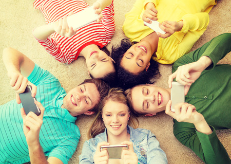 education, technology and happiness concept - group of young smiling people lying down on floor in circle with smartphones photo