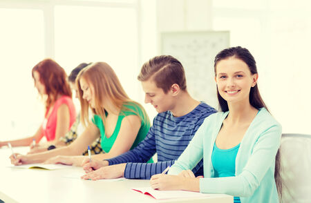 education and school concept - five smiling students with textbooks at school photo