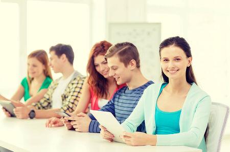 jovenes estudiantes: educaci�n, tecnolog�a e internet concepto - sonrientes estudiantes con computadoras tablet pc en la escuela