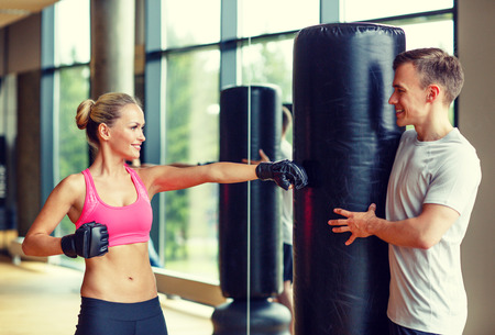 kickboxing: sport, fitness, lifestyle and people concept - smiling woman with personal trainer boxing in gym