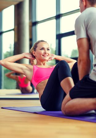 Mujer sonriente con entrenador personal masculino ejercita en gimnasia - deporte, fitness, estilo de vida y concepto de la gente Foto de archivo - 34809600