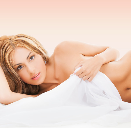 nude young woman: health, sensuality, people and beauty concept - beautiful naked woman lying in bed and covering herself with white sheet over pink background