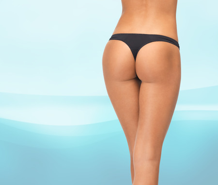 body curve: beauty, people and bodycare concept - close up of female legs in black bikini panties over blue waves background