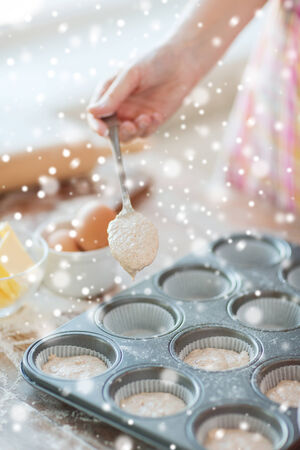 cooking, baking, food and home concept - close up of woman hand filling muffins molds with dough photo