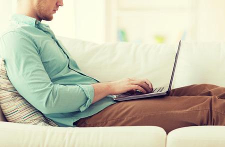 technologie, thuis en lifestyle-concept - close-up van de mens werken met laptop en zittend op de bank thuis