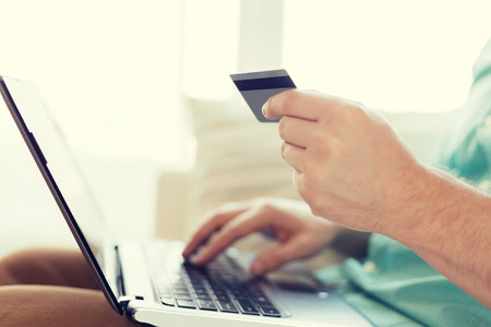 mail order: technology, shopping, banking, home and lifestyle concept - close up of man with laptop computer and credit card at home