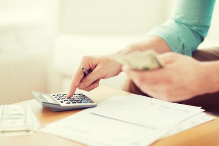 비용 절감, 재정, 경제, 가정 개념 - 가까운 계산기는 돈을 세 집에서 메모를 만드는 남자의