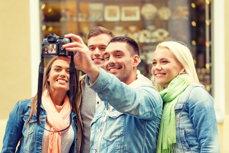 travelers: travel, vacation, technology and friendship concept - group of smiling friends making selfie with digital camera outdoors Stock Photo