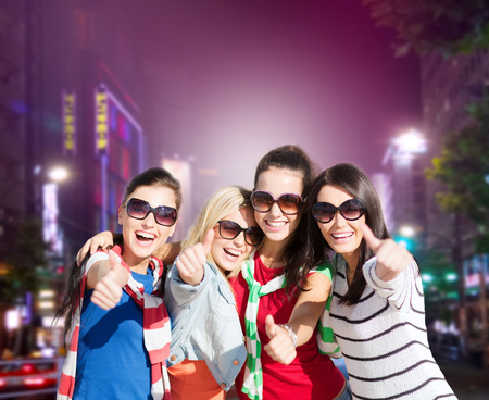 night out: holidays, friendsip, nightlife and happy people concept - happy teenage girls or young women showing thumbs up over night city background Stock Photo