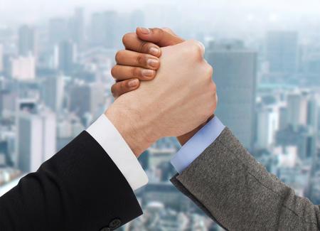 bedrijfsleven, de mensen en de concurrentie concept - close-up van twee mensen handen arm worstelen op ciity achtergrond