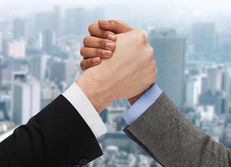 business, people and competition concept - close up of two people hands arm wrestling over ciity background