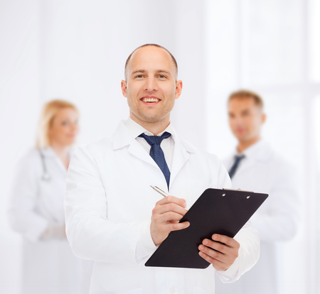 medics: medicine, profession, teamwork and healthcare concept - smiling male doctor with clipboard writing prescription over group of medics