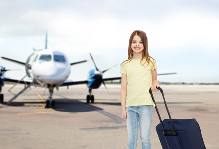 pre teen girls: tourism, holiday, vacation, childhood and transportation concept - smiling little girl with travel bag over airport background Stock Photo