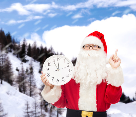 christmas, holidays and people concept - man in costume of santa claus with clock showing twelve pointing finger up over snowy mountains background Stok Fotoğraf