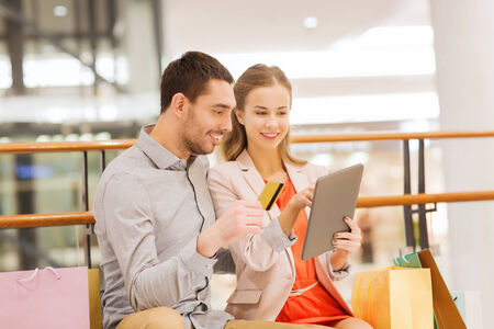 sale, consumerism, technology and people concept - happy young couple with shopping bags and credit card pointing finger to tablet pc computer in mall photo