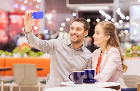 sale, shopping, consumerism, technology and people concept - happy young couple with smartphone taking selfie and drinking coffee or tea at cafe in mall photo
