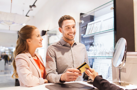 Verlobung: Ausverkauf, Konsum, Einkaufsmöglichkeiten und Menschen Konzept - glückliches Paar mit Kreditkarte im Juweliergeschäft im Einkaufszentrum