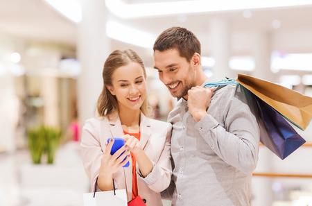 compras: venta, el consumismo, la tecnología y el concepto de la gente - la feliz pareja joven con bolsas y teléfonos inteligentes que hablan en centro comercial