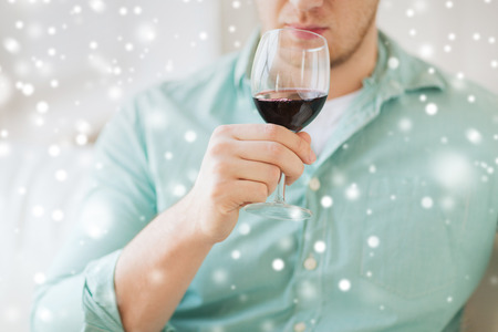 degustating: drinks, winery, leisure and people concept - close up of man with glass drinking red wine at home Stock Photo