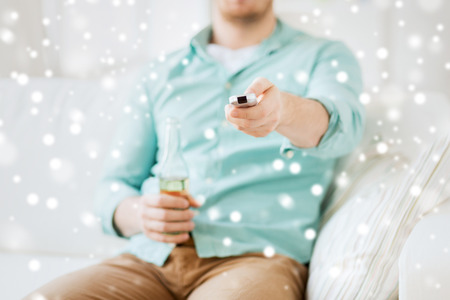 non alcoholic beer: drinks, television, leisure and people concept - man changing tv channels and drinking beer at home Stock Photo