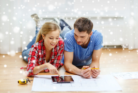 repair, building, renovation, technology and people concept - smiling couple with blueprint looking at tablet pc at home photo