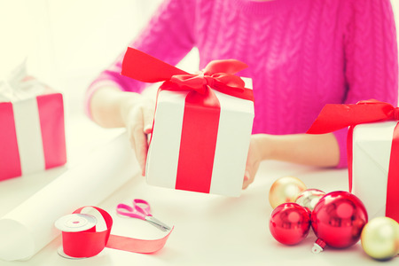balls decorated: holidays, people and celebration concept - close up of woman decorating christmas presents