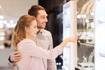 verkoop, consumentisme en de mensen concept - gelukkig paar wijzende vinger naar etalage bij juwelierszaak in winkelcentrum