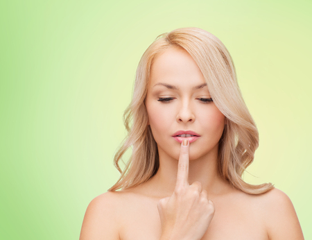 sensitive skin: health, people and beauty concept - beautiful young woman touching her lips over green background