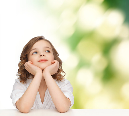 children, childhood, ecology and happy people concept - beautiful girl sitting at table, looking up and dreaming over green background