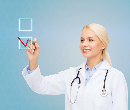 healthcare, medicine and technology concept - smiling young female doctor drawing mark to check box over blue background Stock Photo