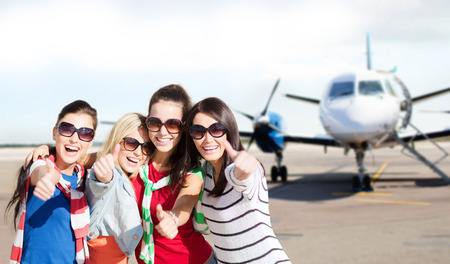 airplane background: travel, holidays, vacation, happy people concept - smiling teenage girls or young women showing thumbs up at airport